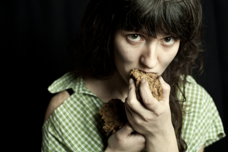 portrait of a poor beggar woman eating bread  photo