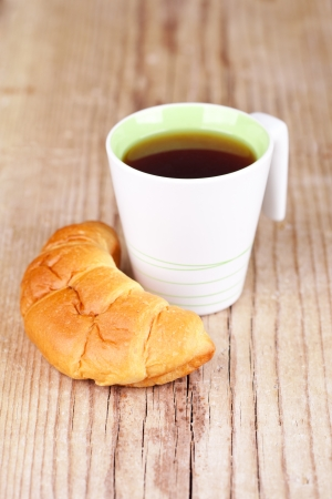 cup of tea and fresh croissant on wooden table for breakfast photo