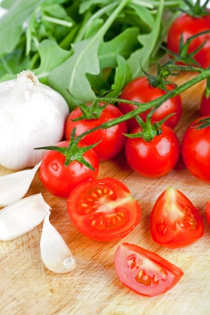 fresh tomatoes, rucola and garlic closeup on wooden board photo