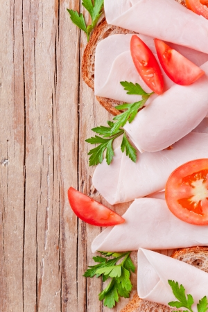 bread with sliced ham, fresh tomatoes and parsley closeup on rustic wooden background photo