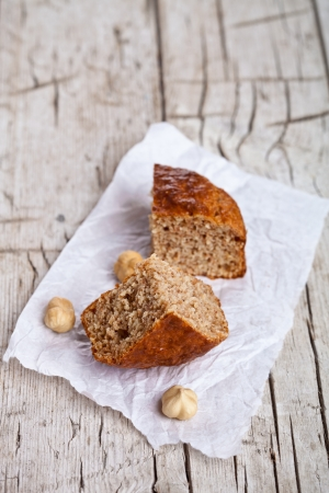 two slices of fresh bun and hazelnuts on rustic wooden table  photo