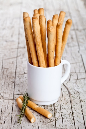 cup with bread sticks grissini and rosemary on rustic wooden background photo