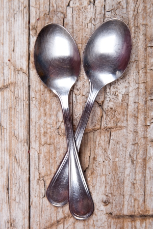 two teaspoons on rustic wooden background photo