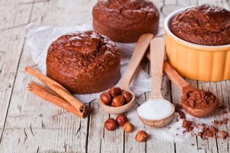 fresh baked browny cakes, sugar, hazelnuts and cocoa powder closeup on rustic wooden table photo