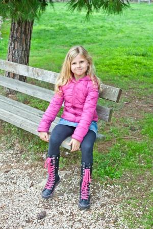 peu jolie fille assise sur un banc dans le parc Banque d'images