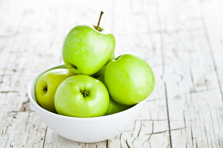 green apple: ripe green apples in bowl on wooden background Stock Photo