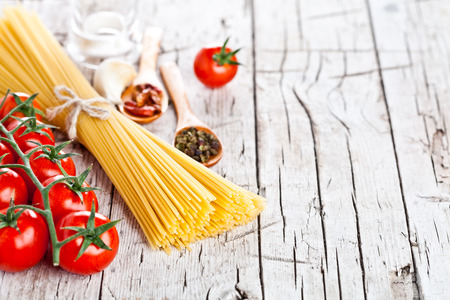 ribbon pasta: uncooked pasta with tomatoes and spices on wooden background