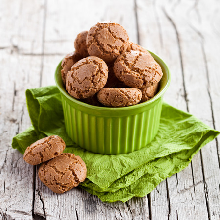 meringue almond cookies in a green bowl on wooden background
