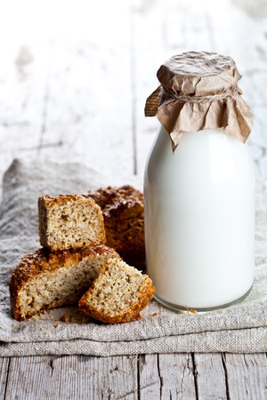 bottle of milk and fresh baked bread on wooden background  photo