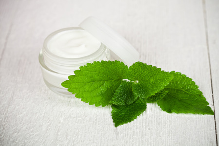 urtica: face cream in glass jar with green leaf of urtica on white wooden