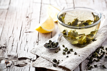 cup of green tea and lemon on rustic wooden table