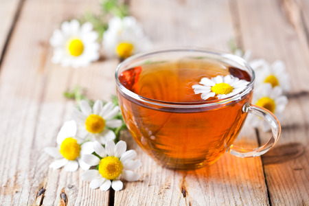 cup of tea with chamomile flowers on rustic wooden background photo