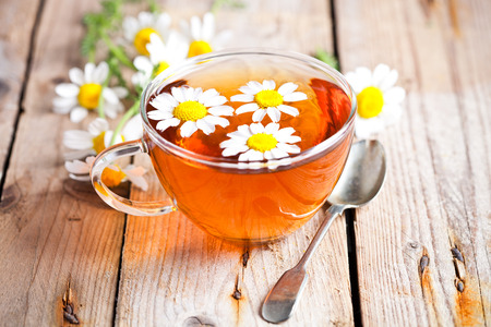 cup of tea with chamomile flowers on rustic wooden background Stockfoto