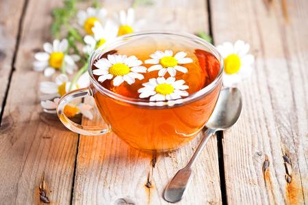 hojas de te: taza de t� con flores de manzanilla en el fondo de madera r�stica