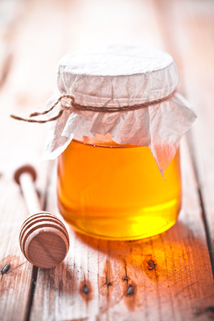 full honey pot and honey stick on rustic wooden board photo