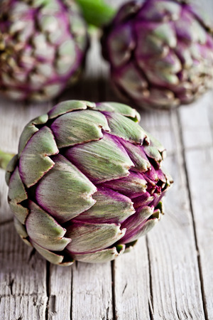 edible leaves: fresh artichokes on rustic wooden background