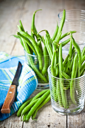 green string beans in glasses, napkin and knife closeup on rustic wooden background photo