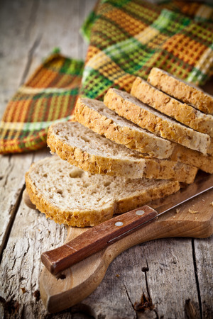 fresh bread slices on wooden board, napkin and knife photo