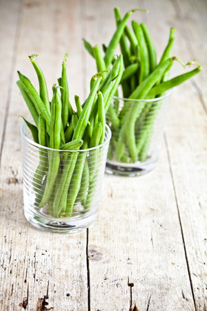 green string beans in glasses on rustic wooden background photo