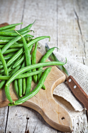 green string beans and knife closeup on wooden board photo