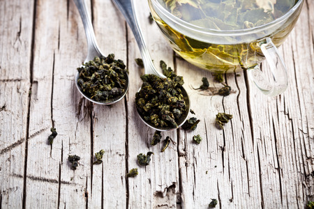 leaves green: cup of green tea and spoons on rustic wooden table  Stock Photo