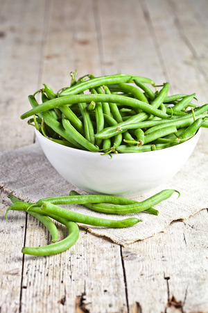 green string beans in a bowl on rustic wooden table photo