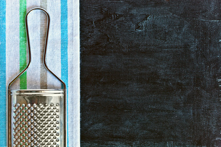 metal grater: metal grater and tablecloth over blackboard background