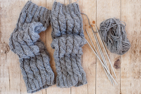 legwarmers: wool grey legwarmers knitting needles and yarn on wooden background Stock Photo