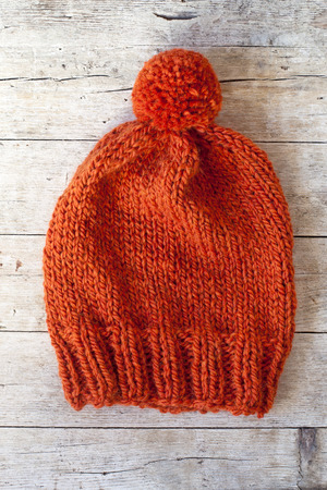pompom: wool orange pompom hat closeup on wooden background