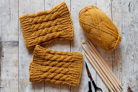 legwarmers: wool yellow legwarmers, scissors, knitting needles and yarn on wooden background