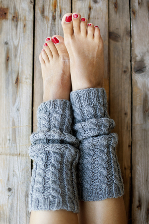Womans legs in knitted gray legwarmers closeup on wooden background.