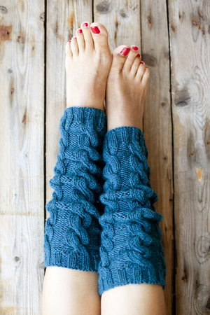 Womans legs in knitted blue legwarmers closeup on wooden background. Stock Photo