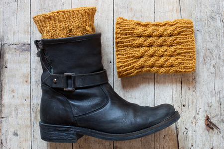 black leather boot and knitted wood legwarmers on wooden background