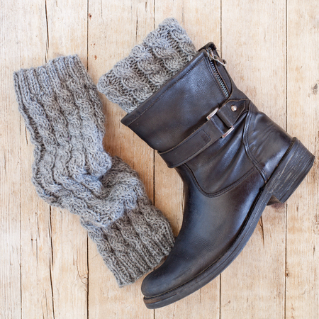 black leather boot and grey knitted wood legwarmers on wooden background