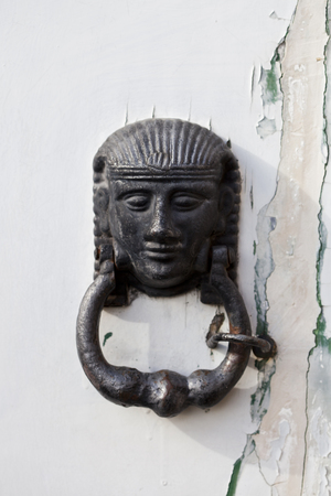 Ancient italian door knocker on grunge background.
