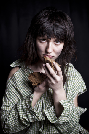 Portrait of a poor beggar woman with a piece of bread in her hands.
