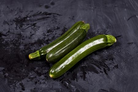 Fresh green organic zucchini and water on black background.