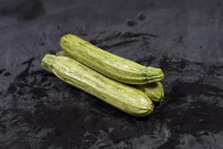 Fresh green wet zucchini on blackboard background.