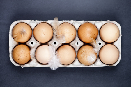 Farm chicken eggs in cardboard container and feathers on black background. Top view.