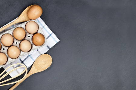 Fresh eggs and kitchen utensil on backboard background. Eggs, wooden spoon, whisker, towel and other cooking baking ingredients for cake, pastry or cookies. Top view with copy space. Standard-Bild
