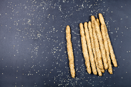 Italian grissini bread sticks with sesame seeds on black board background. Fresh italian snack. Top view with copy space. Reklamní fotografie