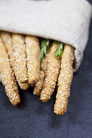 Italian grissini or salted bread sticks with rosemary herb on linen napkin on black board background. Fresh italian snack.