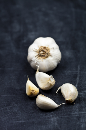Fresh raw organic garlic on black board background. Фото со стока