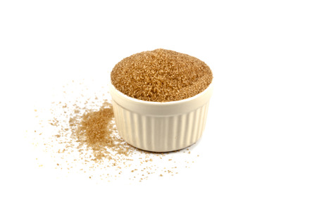 Brown cane sugar in ceramic bowl isolated on white background. Sweet sugar in bowl. Stock fotó