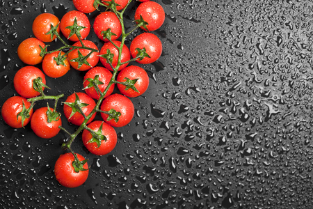 Fresh organic cherry tomatoes bunch closeup on black wet background. Top view with copy space.