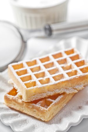 Gaufrettes belges avec du sucre en poudre sur une assiette en céramique et une passoire sur un tableau blanc. Gaufrettes fraîchement cuites. Banque d'images