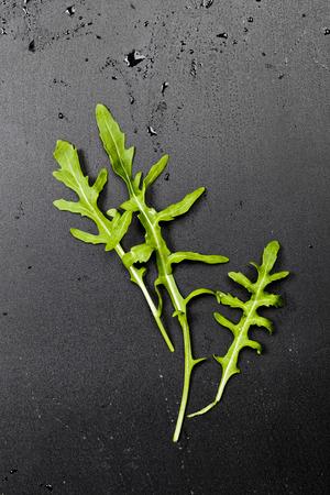 Three green fresh rucola or arugula leaves on black wet background.