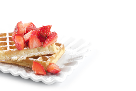 Belgium waffers with sugar powder and strawberries on ceramic plate on white table. Fresh baked wafers with copy space. Banco de Imagens