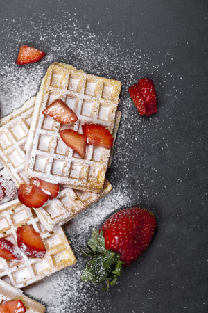 Belgium waffers with strawberries and sugar powder on black board background. Banco de Imagens