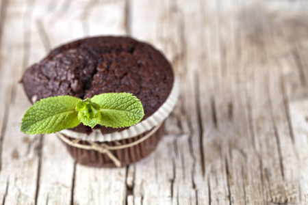Chocolate dark muffins with mint leaves on rustic wooden table. With copy space.